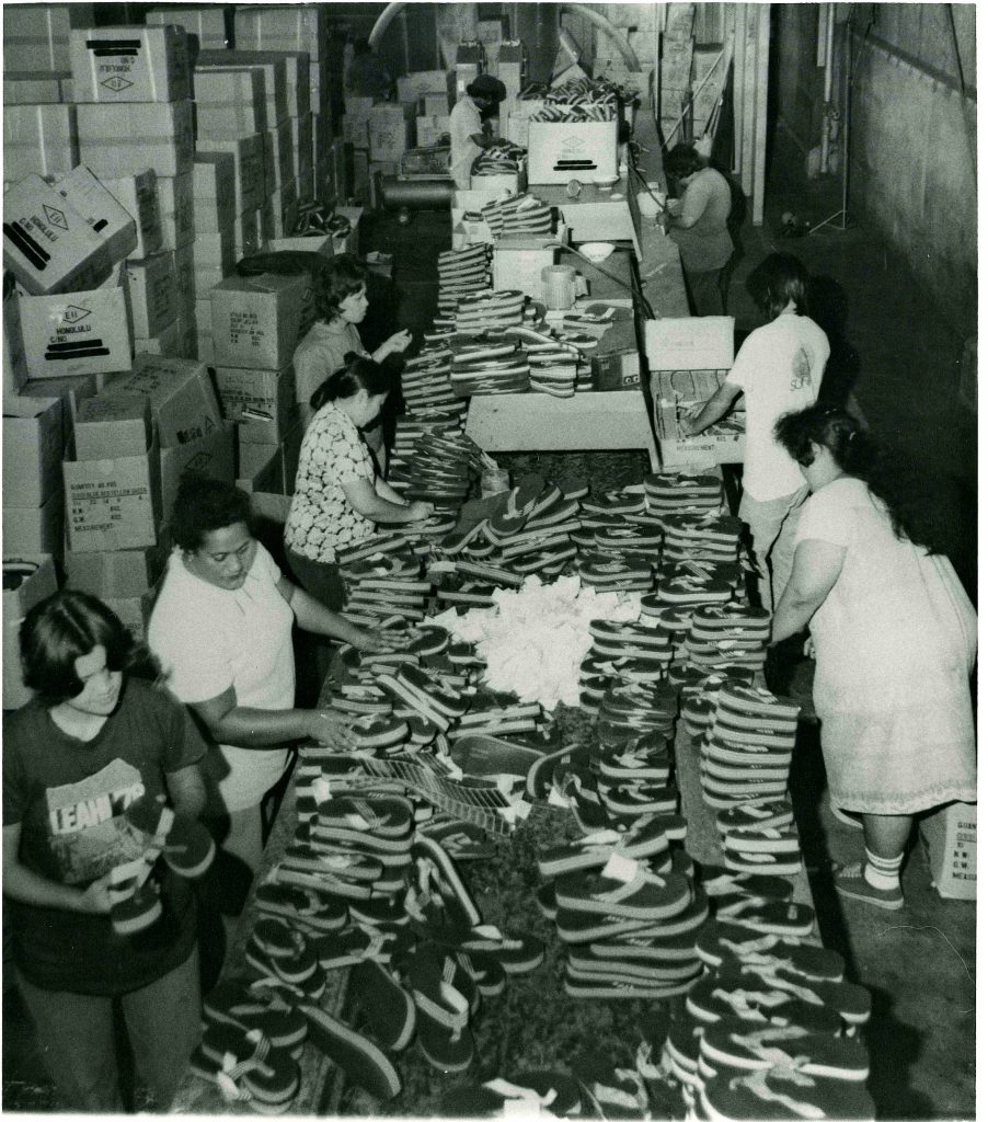 Workers in the warehouse packing slippers.