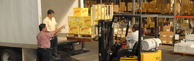 forklift operator loading boxes into truck inside FTZ warehouse